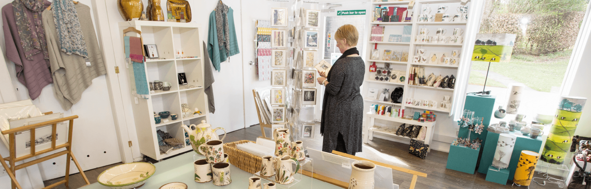 a woman browses a gift shop at one of Dumfries and Galloway's Venues